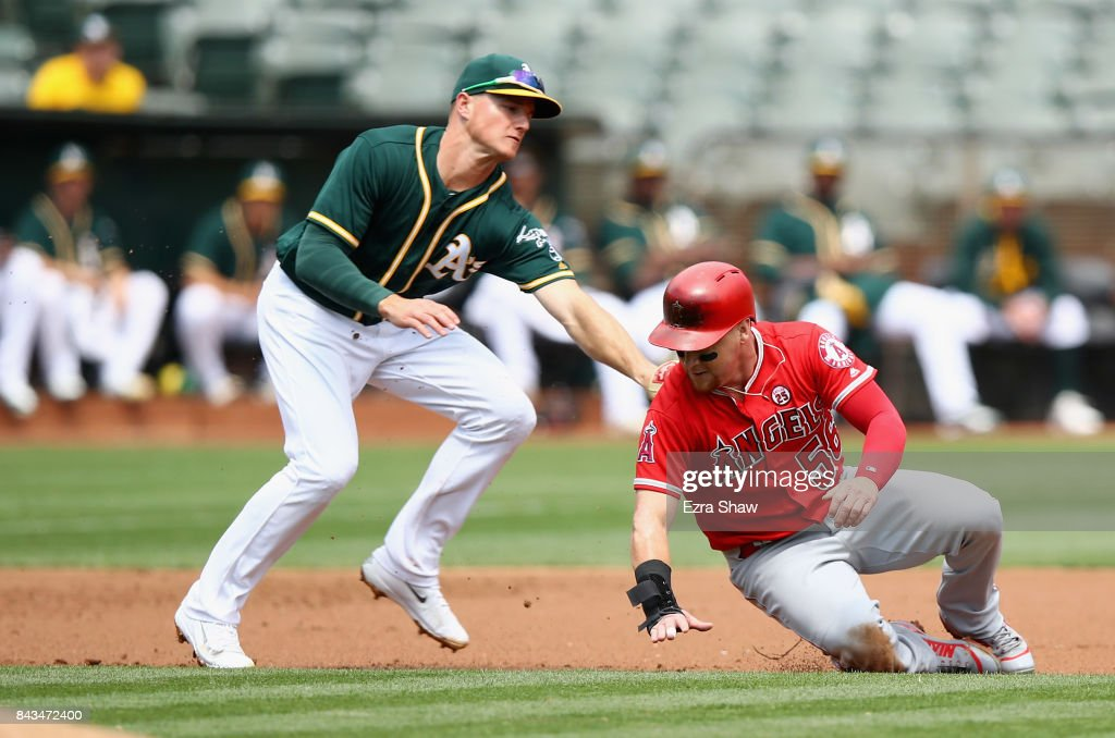 Matt Chapman #26 of the Oakland Athletics tags out Kole Calhoun #56 of the Los Angeles Angels in a rundown in the second inning at Oakland Alameda Coliseum on September 6, 2017 in Oakland, California.