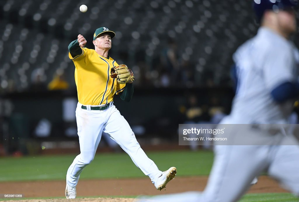 Matt Chapman #26 of the Oakland Athletics throws off balance to first base throwing out Christian Arroyo #21 of the Tampa Bay Rays in the top of the seventh inning at the Oakland Alameda Coliseum on May 30, 2018 in Oakland, California.