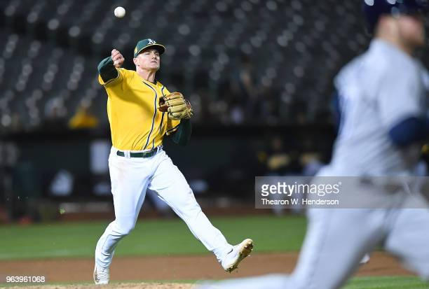 Matt Chapman of the Oakland Athletics throws off balance to first base throwing out Christian Arroyo of the Tampa Bay Rays in the top of the seventh...