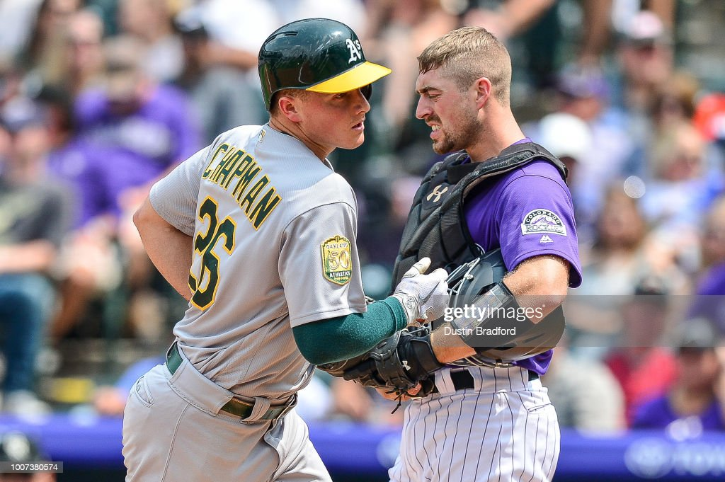 Matt Chapman #26 of the Oakland Athletics touches home plate as Tom Murphy #23 of the Colorado Rockies reacts after Chapman hit a fourth inning solo homerun during interleague play at Coors Field on July 29, 2018 in Denver, Colorado.
