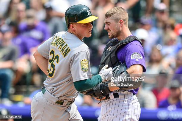 Matt Chapman of the Oakland Athletics touches home plate as Tom Murphy of the Colorado Rockies reacts after Chapman hit a fourth inning solo homerun...