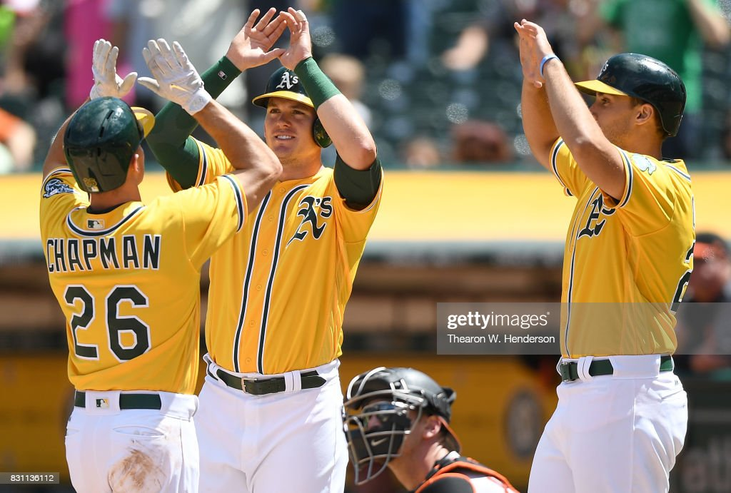 Matt Chapman #26, Ryon Healy #25 and Matt Olson #28 of the Oakland Athletics celebrates after Chapman hit a three-run homer against the Baltimore Orioles in the bottom of the fourth inning at Oakland Alameda Coliseum on August 13, 2017 in Oakland, California.
