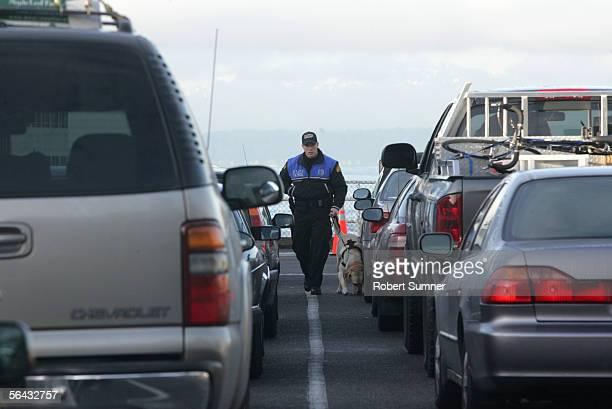 Matt Chatterton of the Washington State Patrol with his dog checks cars waiting to board a Washington State Ferry to Bainbridge Island December 14...