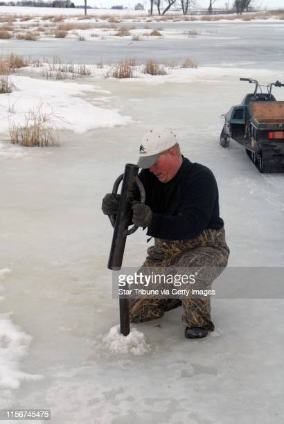 Matt Chouinard of Delta Waterfowl pounds a steel post into the bottom of a wetland The post will hold a hen house mallard nesting structure Chouinard...