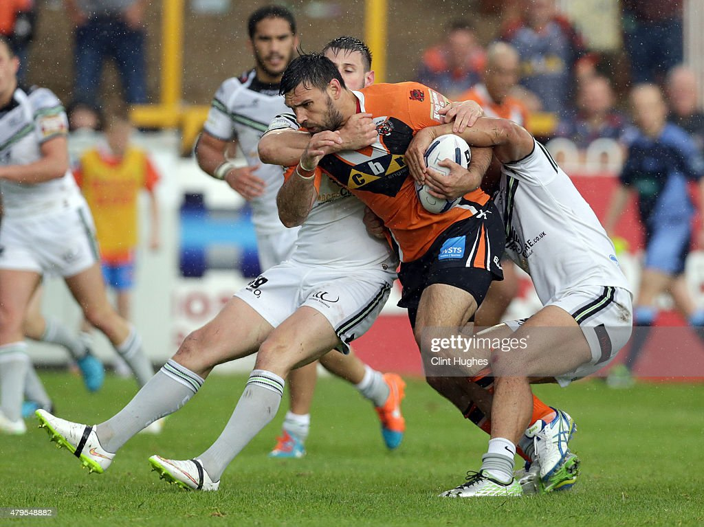 Matt Cook of Castleford Tigers is tackled by a determined Widnes Vikings defence during the First Utility Super League match between Castleford Tigers and Widnes Vikings at The Jungle on July 5, 2015 in Castleford, England.