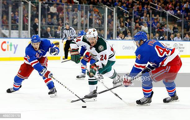 Matt Cooke of the Minnesota Wild tries to split the defense of Michael Del Zotto and Justin Falk of the New York Rangers during the first period at...