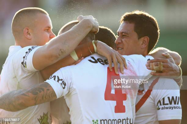 Matt Cooper of the Dragons celebrates with his team mates after scoring a try during the round six NRL match between the Wests Tigers and the St...