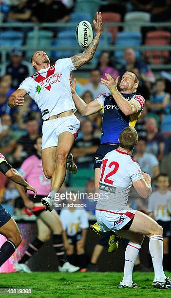 Matt Cooper of the Dragons contests a high ball with Brent Tate of the Cowboys during the round nine NRL match between the North Queensland Cowboys...