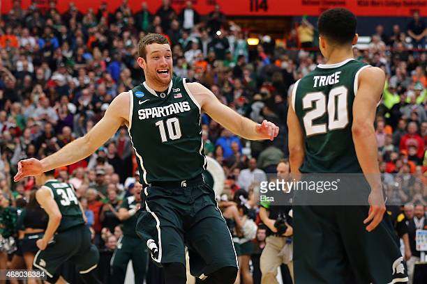 Matt Costello and Travis Trice of the Michigan State Spartans celebrate defeating the Louisville Cardinals 76 to 70 in overtime of the East Regional...