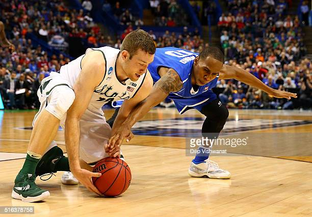 Matt Costello of the Michigan State Spartans and Jaqawn Raymond of the Middle Tennessee Blue Raiders compete for a loose ball in the second half...