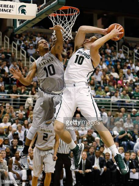 Matt Costello of the Michigan State Spartans gets a second half shot off around the defense of Duke Mondy of the Oakland Golden Grizzlies at the Jack...