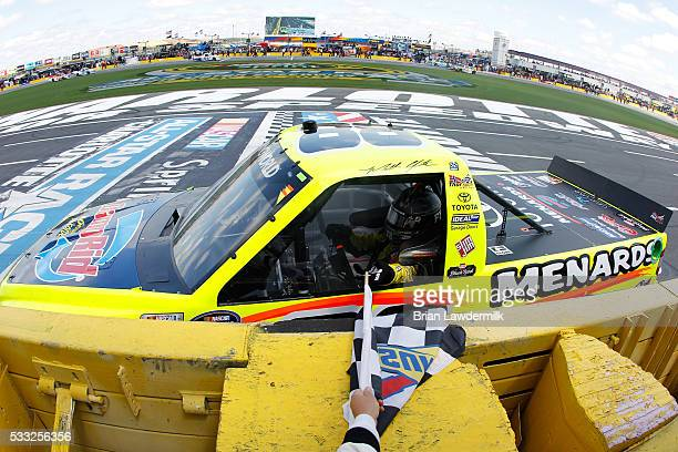 Matt Crafton driver of the Damp Rid/Menards Toyota celebrates with the checkered flag after winning the NASCAR Camping World Truck Series North...