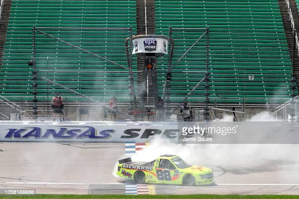 Matt Crafton, driver of the Ford, celebrates with a burnout after winning the NASCAR Gander RV & Outdoors Truck Series e.p.t 200 at Kansas Speedway...