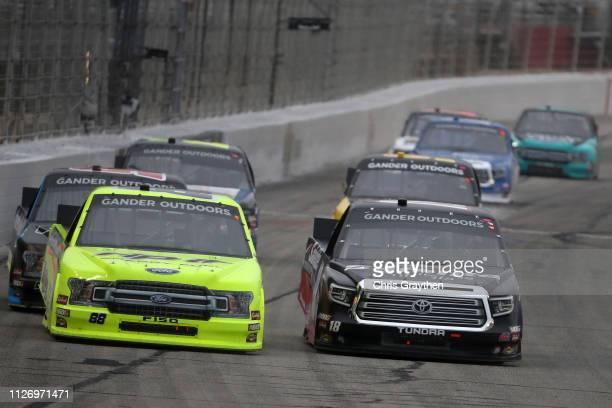 Matt Crafton driver of the Rip It/Menards Ford races Harrison Burton driver of the Safelite AutoGlass Toyota during the NASCAR Gander Outdoors Truck...