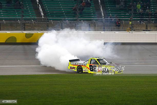 Matt Crafton driver of the Slim Jim/Menards Toyota celebrates with a burnout after winning the NASCAR Camping World Truck Series Toyota Tundra 250 at...