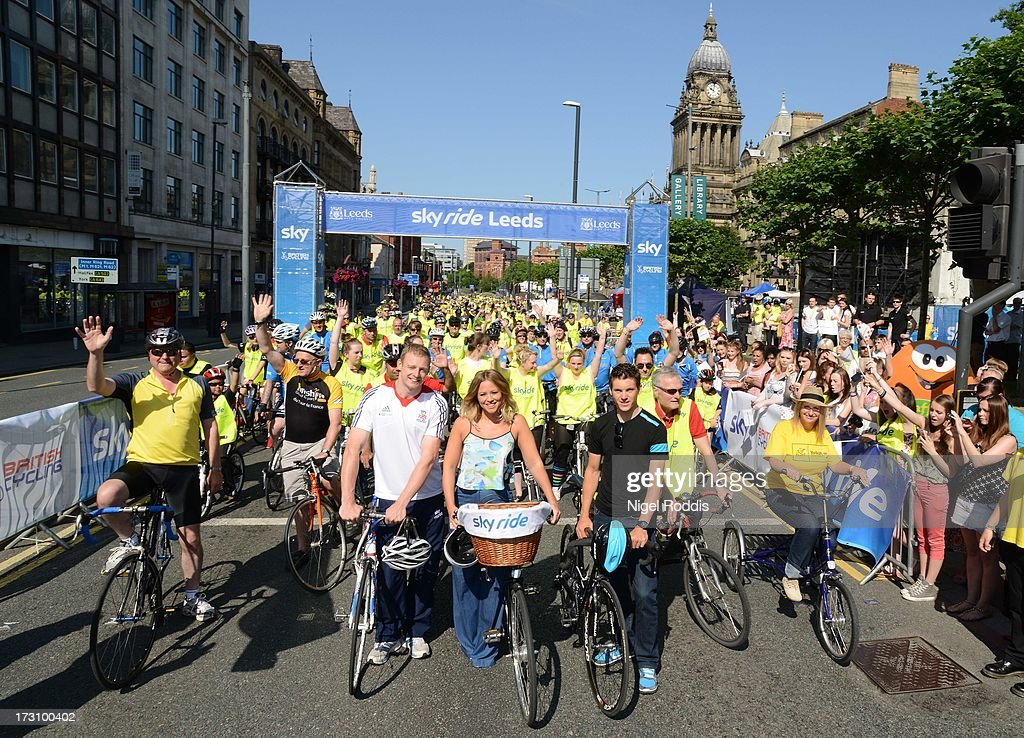 Matt Crampton (L) and Ben Swift (R) with Kimberley Walsh attend Sky Ride in Leeds - a free, fun, family cycling event from Sky and British Cycling held in partnership with Leeds City Council, offering people of all ages and abilities the chance to cycle around a traffic-free city on July 7, 2013 in Leeds, England. The ride celebrated the fact that the Tour de France will start in Leeds in 2014. Find a free organised bike ride near you and see how you can get involved at www.goskyride.com - there's something for everyone.