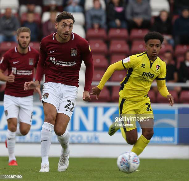 Matt Crooks of Northampton Town moves forward with the ball away from Jacob Maddox of Cheltenham Town during the Sky Bet League Two match between...