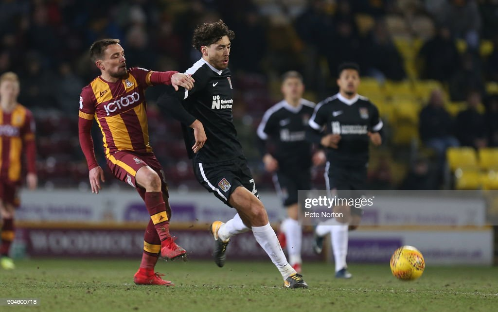 Matt Crooks of Northampton Town plays the ball away from Paul Taylor of Bradford City during the Sky Bet League One match between Bradford City and Northampton Town at Northern Commercials Stadium, Valley Parade on January 13, 2018 in Bradford, England.