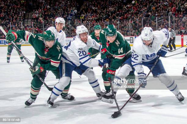Matt Cullen and Joel Eriksson Ek of the Minnesota Wild battle for the puck with Dominic Moore and Josh Leivo of the Toronto Maple Leafs during the...