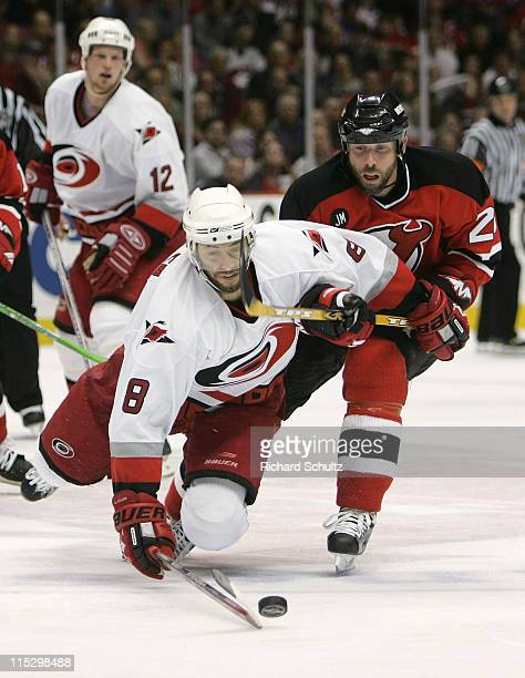 Matt Cullen of the Carolina Hurricanes dives for the puck as Grant Marshall of the New Jersey Devils defends during the second period of game three...