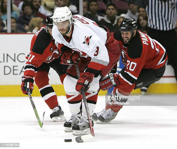 Matt Cullen of the Carolina Hurricanes moves past John Madden and Jay Pandolfo of the New Jersey Devils during the second period of game three in the...
