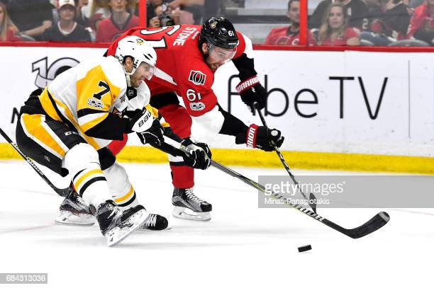 Matt Cullen of the Pittsburgh Penguins and Mark Stone of the Ottawa Senators skate for the puck during the third period in Game Three of the Eastern...