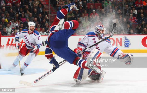Matt D'Agostini of the Montreal Canadiens goes airborn after colliding with Henrik Lundqvist of the New York Rangers at the Bell Centre on December 4...