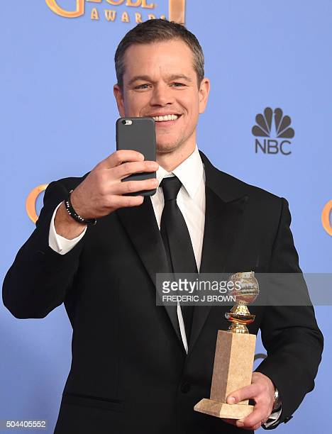 TOPSHOT Matt Damon takes a selfie in the press room with the award for Best Actor in a Motion Picture Musical or Comedy for 'The Martian' January 10...