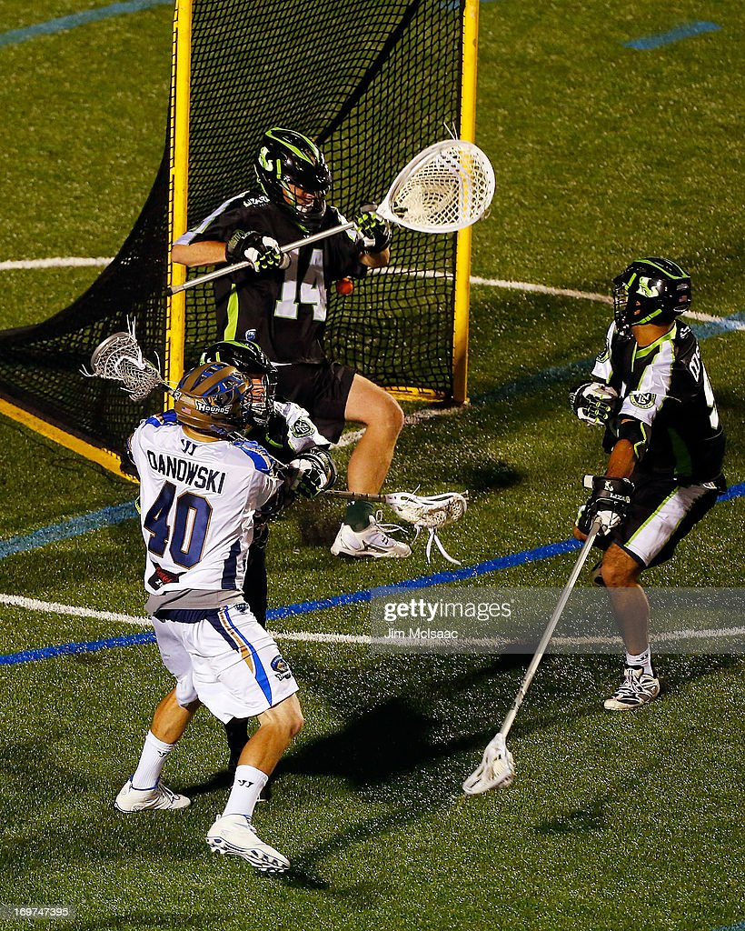 Matt Danowski #40 of the Charlotte Hounds scores his second goal against Drew Adams #14 and CJ Costabile #96 of the New York Lizards during their Major League Lacrosse game at Shuart Stadium on May 31, 2013 in Uniondale, New York.