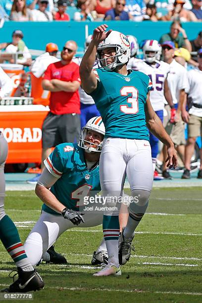 Matt Darr looks up with Andrew Franks of the Miami Dolphins as he kick a field goal against the Buffalo Bills on October 23 2016 at Hard Rock Stadium...