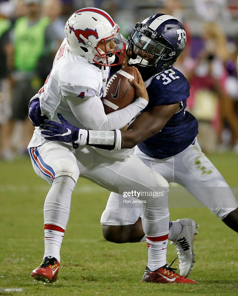 Matt Davis #4 of the Southern Methodist Mustangs is sacked by Travin Howard #32 of the TCU Horned Frogs in the second half at Amon G. Carter Stadium on September 19, 2015 in Fort Worth, Texas.