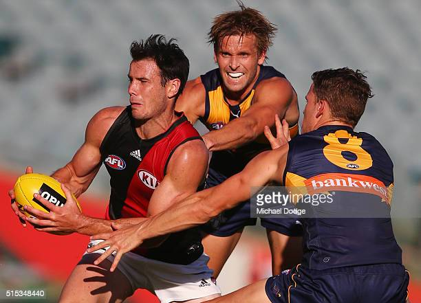 Matt Dea is tackled by Mark LeCras and Jack Redden of the Eagles during the NAB Challenge AFL match between the West Coast Eagles and the Essendon...