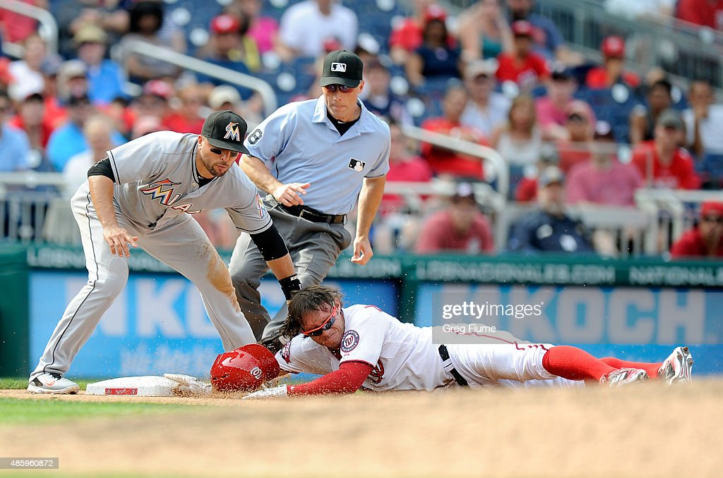 Matt den Dekker #21 of the Washington Nationals is tagged out at third base in the eighth inning by Martin Prado #14 of the Miami Marlins at Nationals Park on August 30, 2015 in Washington, DC.