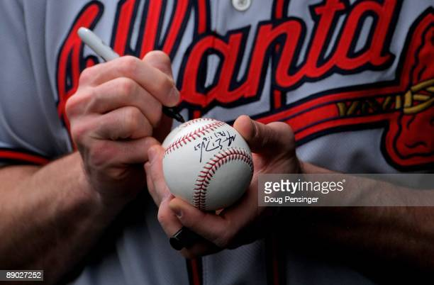 Matt Diaz of the Atlanta Braves autographs a ball for a fan while in the dugout against the Colorado Rockies during MLB action at Coors Field on July...