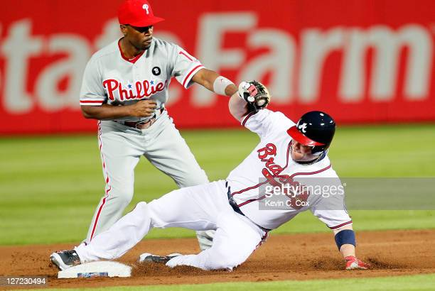 Matt Diaz of the Atlanta Braves slides into second base safely under the tag of Jimmy Rollins of the Philadelphia Phillies after hitting a double in...