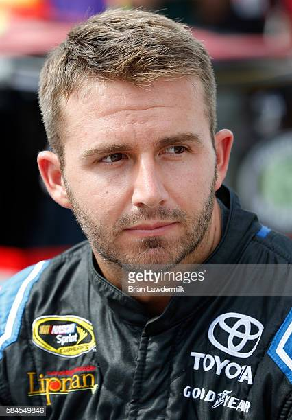 Matt DiBenedetto driver of the EJ Wade Construction Toyota stands on the grid during qualifying for the NASCAR Sprint Cup Series Pennsylvania 400 at...