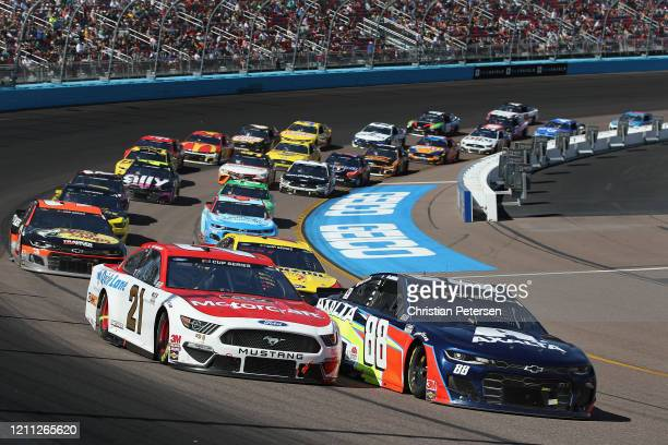 Matt DiBenedetto driver of the Motorcraft/Quick Lane Ford and Alex Bowman driver of the Axalta Chevrolet lead during the NASCAR Cup Series FanShield...