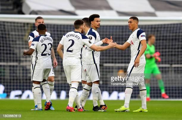 Matt Doherty, Dele Alli and Carlos Vinicius of Tottenham Hotspur shake hands prior to the UEFA Europa League Round of 32 match between Tottenham...