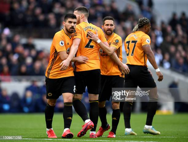 Matt Doherty of Wolverhampton Wanderers celebrates with teammates Ruben Neves and Joao Moutinho after scoring his sides first goal during the Premier...