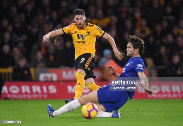 Matt Doherty of Wolverhampton Wanderers shoots under pressure from Marcos Alonso of Chelsea during the Premier League match between Wolverhampton...