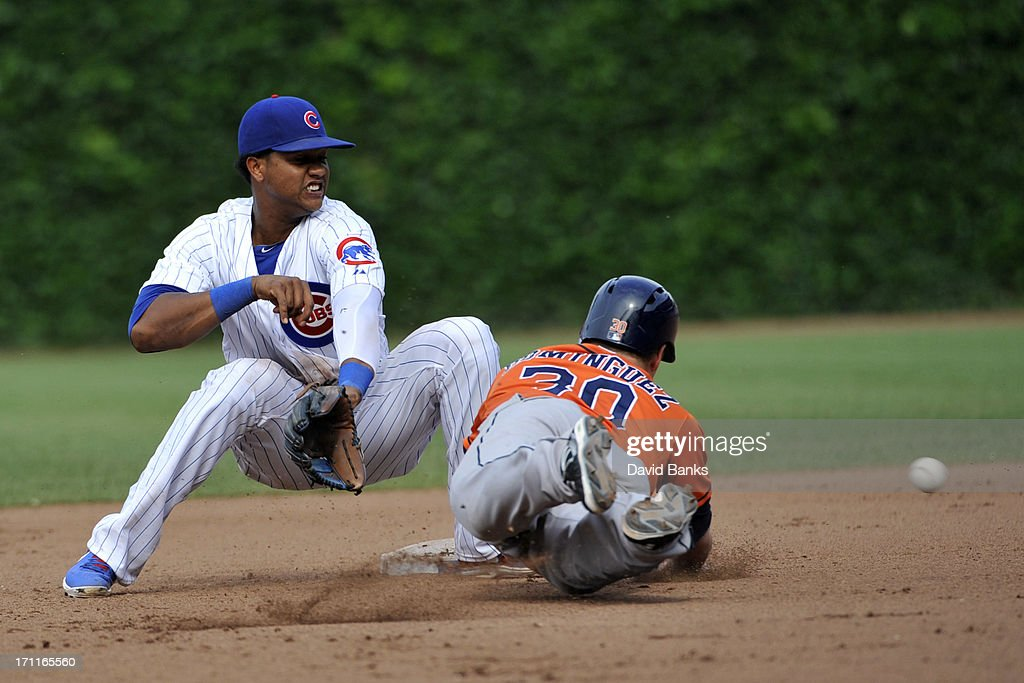 Matt Dominguez #30 of the Houston Astros dives back safely into second base on a pick-off attempt as Starlin Castro #13 of the Chicago Cubs takes the throw during the seventh inning on June 22, 2013 at Wrigley Field in Chicago, Illinois.
