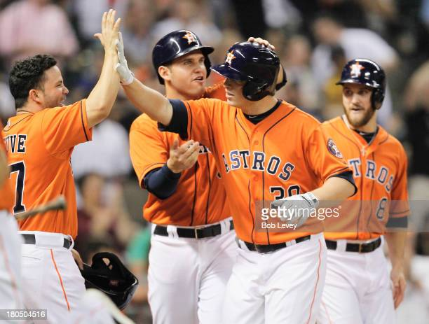 Matt Dominguez of the Houston Astros receives high fives from Jose Altuve Trevor Crowe and Brandon Laird after hitting a grand slam in the fifth...