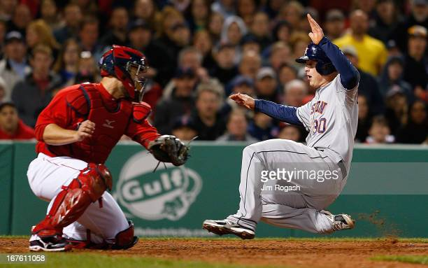 Matt Dominguez of the Houston Astros slides into home past the tag of David Ross of the Boston Red Sox in th 5th inning at Fenway Park on April 26...