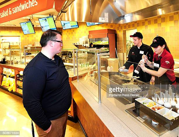 Matt Drost of Randolf waits for Line cook Natasha Worrey to complete his stir fry selection at the new Food Court at Hannaford Brothers near Backcove