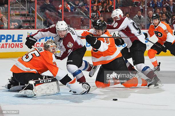 Matt Duchene and Ryan O'Reilly of the Colorado Avalanche battle for a loose puck against Steve Mason and Braydon Coburn of the Philadelphia Flyers at...