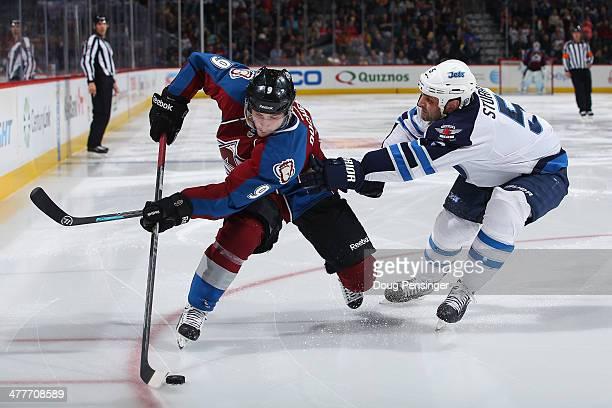 Matt Duchene of the Colorado Avalanche controls the puck against Mark Stuart of the Winnipeg Jets at Pepsi Center on March 10 2014 in Denver Colorado