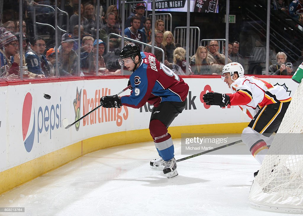 Matt Duchene #9 of the Colorado Avalanche plays the puck off the boards against Mikael Backlund #11 of the Calgary Flames at the Pepsi Center on January 2, 2016 in Denver, Colorado. The Flames defeated the Avalanche 4-0.