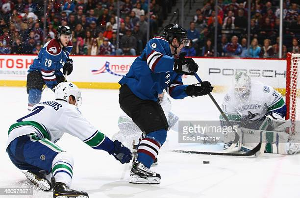 Matt Duchene of the Colorado Avalanche takes a shot as goalie Eddie Lack of the Vancouver Canucks makes a save and Dan Hamhuis of the Vancouver...