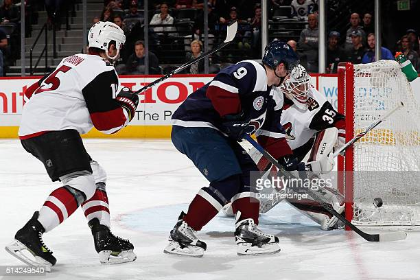 Matt Duchene of the Colorado Avalanche takes a wide shot as goalie Louis Domingue of the Arizona Coyotes defends the goal and Boyd Gordon of the...