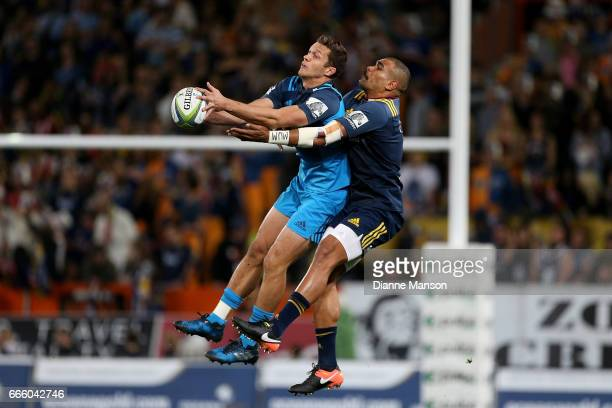 Matt Duffie of the Blues and Patrick Osborne of the Highlanders compete for the high ball during the round seven Super Rugby match between the...